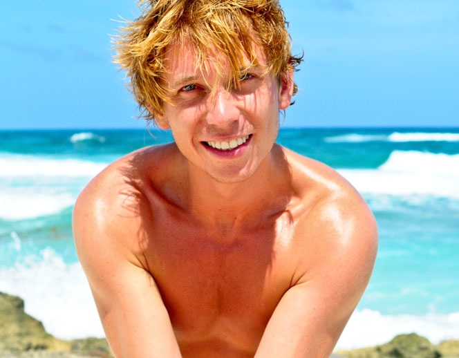Tanned Blond Boy Showing Tattoo On A Beach