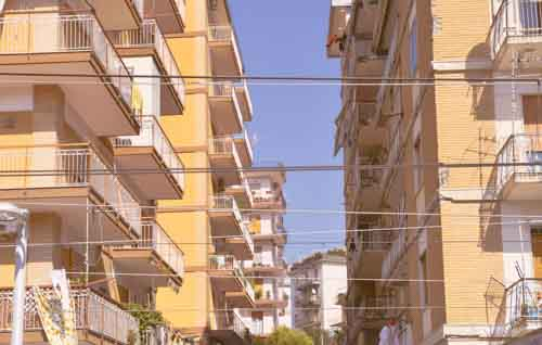 European Yellow Apartments With Balconys In The Sun