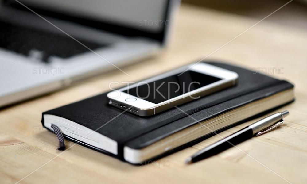 Smart Phone Notebook Pen And Open Laptop On Desk