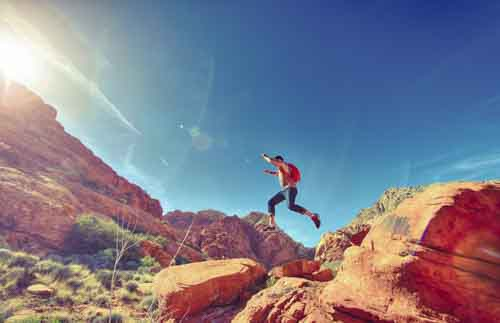 Athletic Man Jumping Between Rocks In Outdoor National Park
