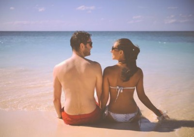 Cute Man And Woman Sitting On A Beach With Sea