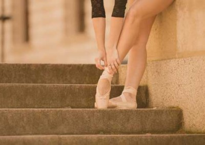 Girl Putting On Ballet Pointe Shoes For Dance