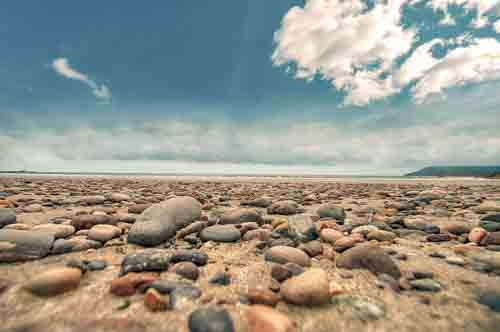 Dramatic Landscape Of Pebbles On Beach With Blue Sky And Clouds