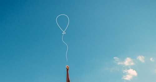 Woman's Hand Reaching With Hope To Catch A Balloon Against Blue Sky