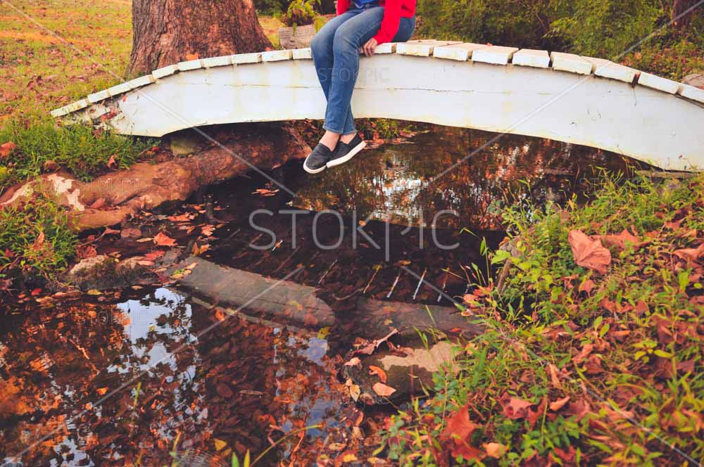 Girl Sitting On Bridge With Stream And Fall Leaves