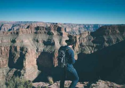 Man Wearing Cowboy Hat Looking At Grand Canyon
