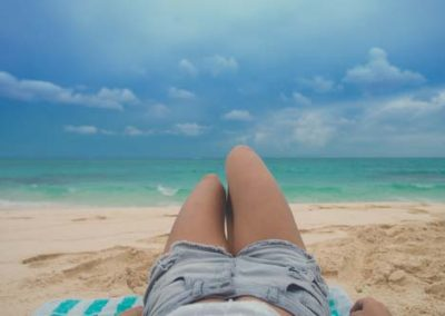 Lifestyle Girl laying on Beach With Jean Shorts