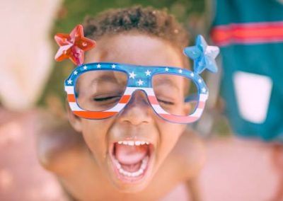 African american young boy with big smile wearing fun American flag glasses