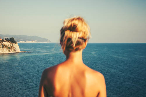 Blonde woman looking out at awesome view of the ocean