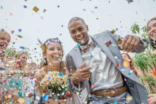Happy Couple Getting Married With Confetti And Flowers