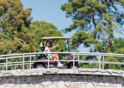 Man And Woman Driving A Golf Cart In Summer