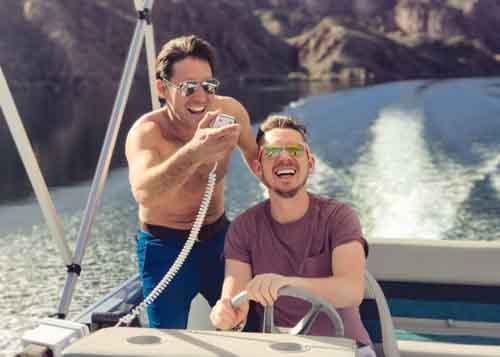 Two Men Driving A Spead Boat Laughing And Having Fun