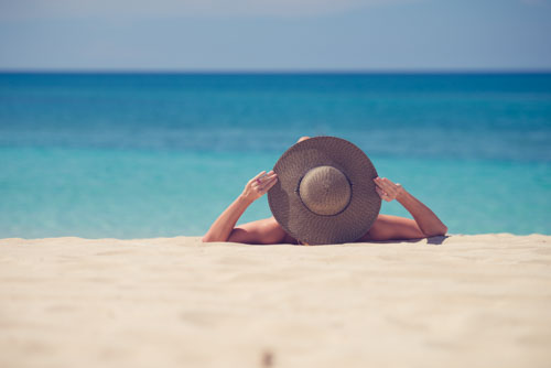 Woman Wearing Sun Hat On A White Sandy Beach