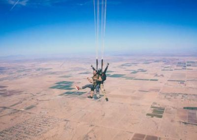 Two men sky diving over the desert with bright summer blue sky