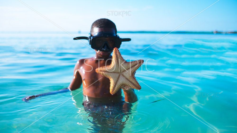 Boy holding star fish in the ocean wearing goggles