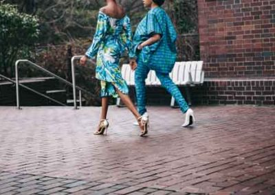 Afican American women walking together wearing bright blue outfits and heels