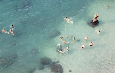 Group of people and friends playing and having fun in the ocean